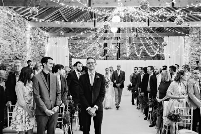 Groom smiling as the bride arrives at the ceremony at New House Farm in Lorton