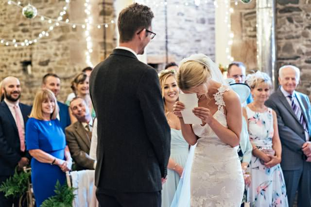Bride laughing as she tries to read her vows