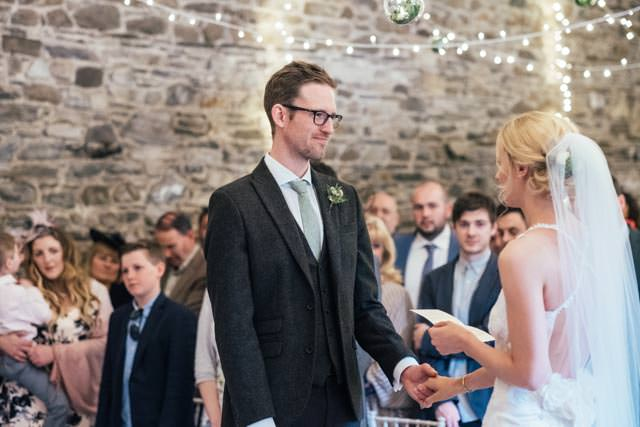 Groom looking lovingly at his bride as she reads her vows