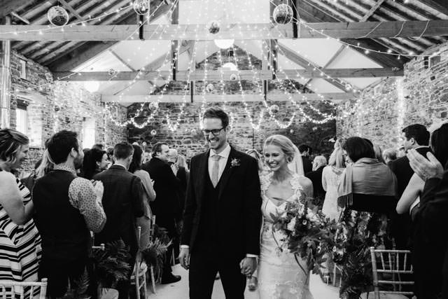Bride and groom smiling as they leave the wedding cermony at New House Farm in Lorton