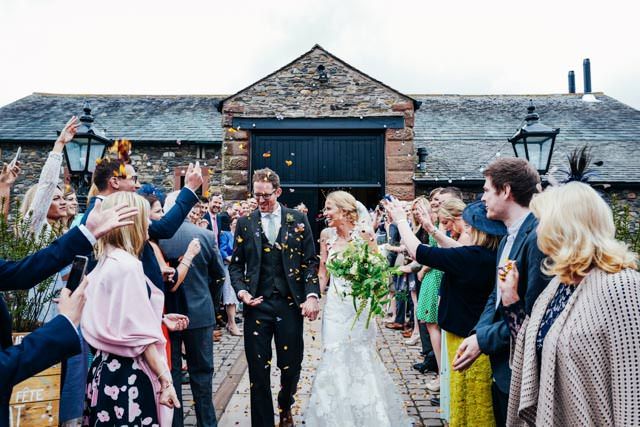 Wedding guests throwing confetti over bride and groom at New House Farm in Lorton