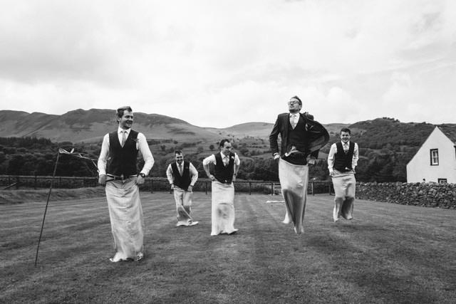 Groom and his groomsmen having a sack race at New House Farm in Lorton