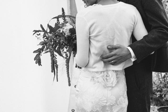 Back shot of the groom with his arm around his wife
