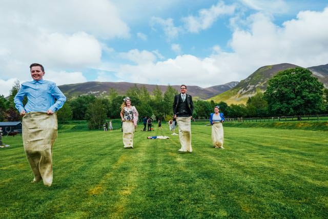 Groom and guests having a sack race