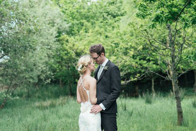 Bride and groom cuddling in the garden at New House Farm