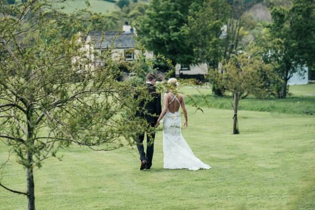 Bride and groom walking through the trees at New House Farm