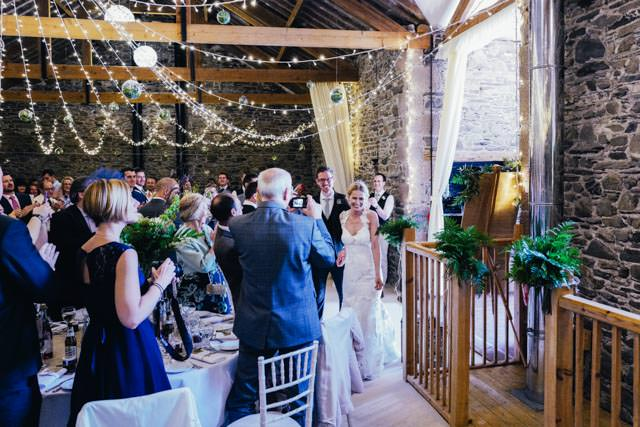 Bride and Groom entering the reception whilst guests clap and cheer
