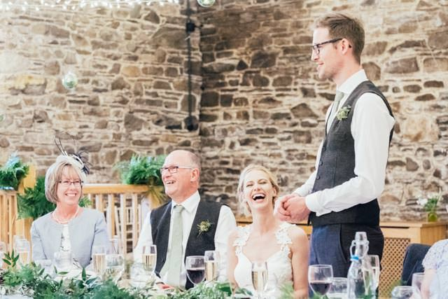 Bride laughing whilst groom makes his speech