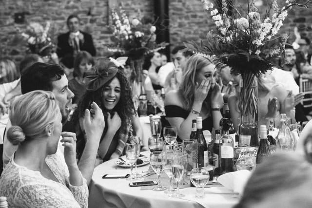 Wedding guests laughing at the best mans speech