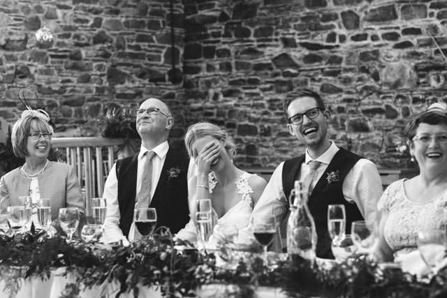 Bride covering her face and laughing at the best mans speech.