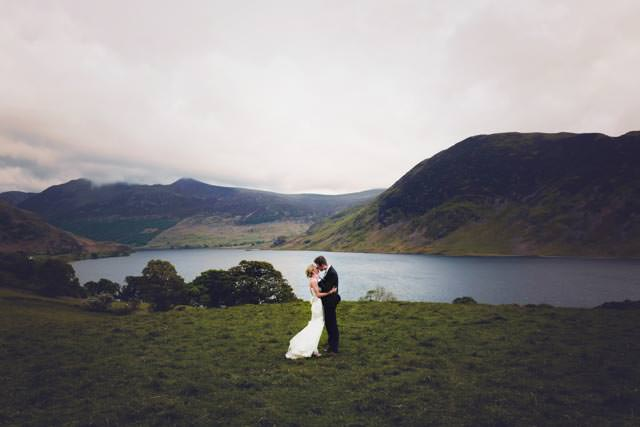 Bride and groom kissing overlooking buttermere lake