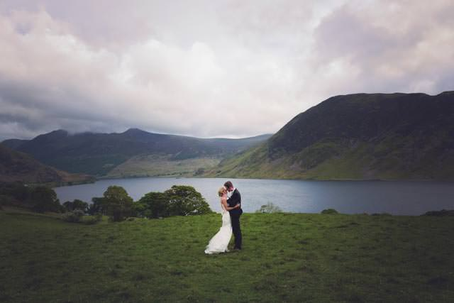 Bride and groom kissing overlooking Buttermere Lake in Cumbria