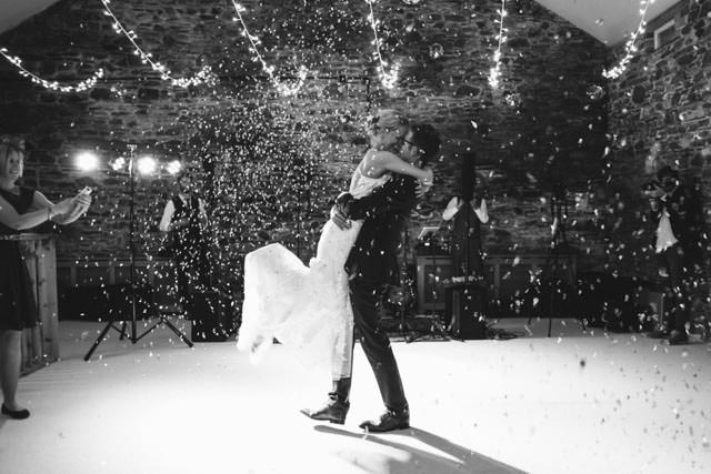 Bride and groom dancing whilst confetti cannons go off