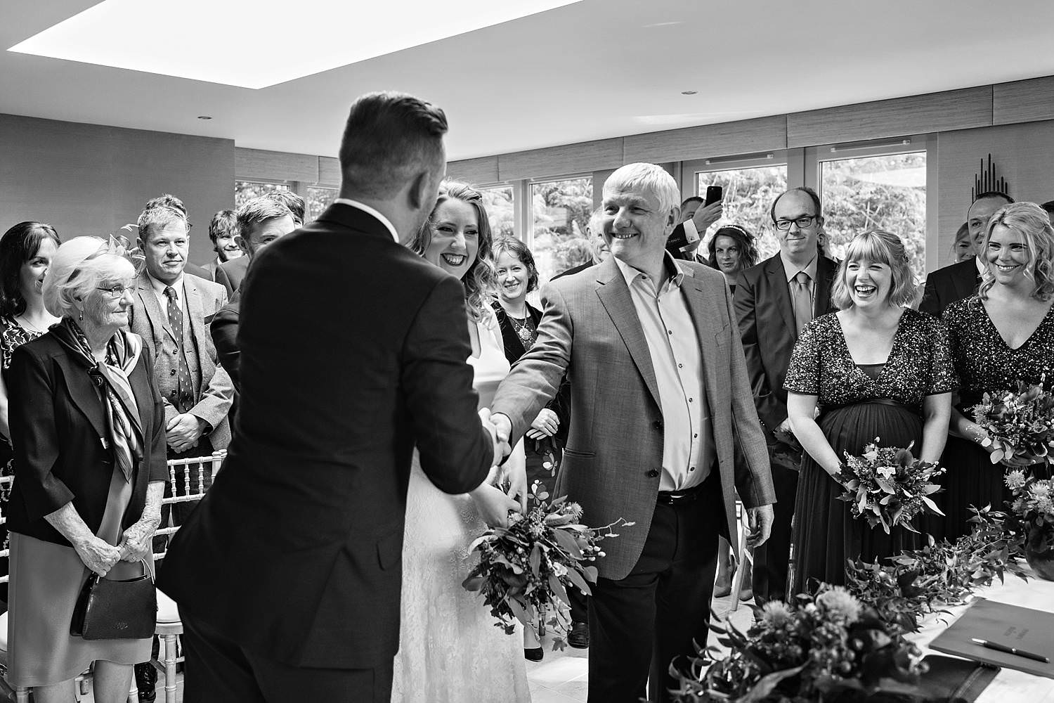 Bride's dad shaking the grooms hand as he gives his daughter away