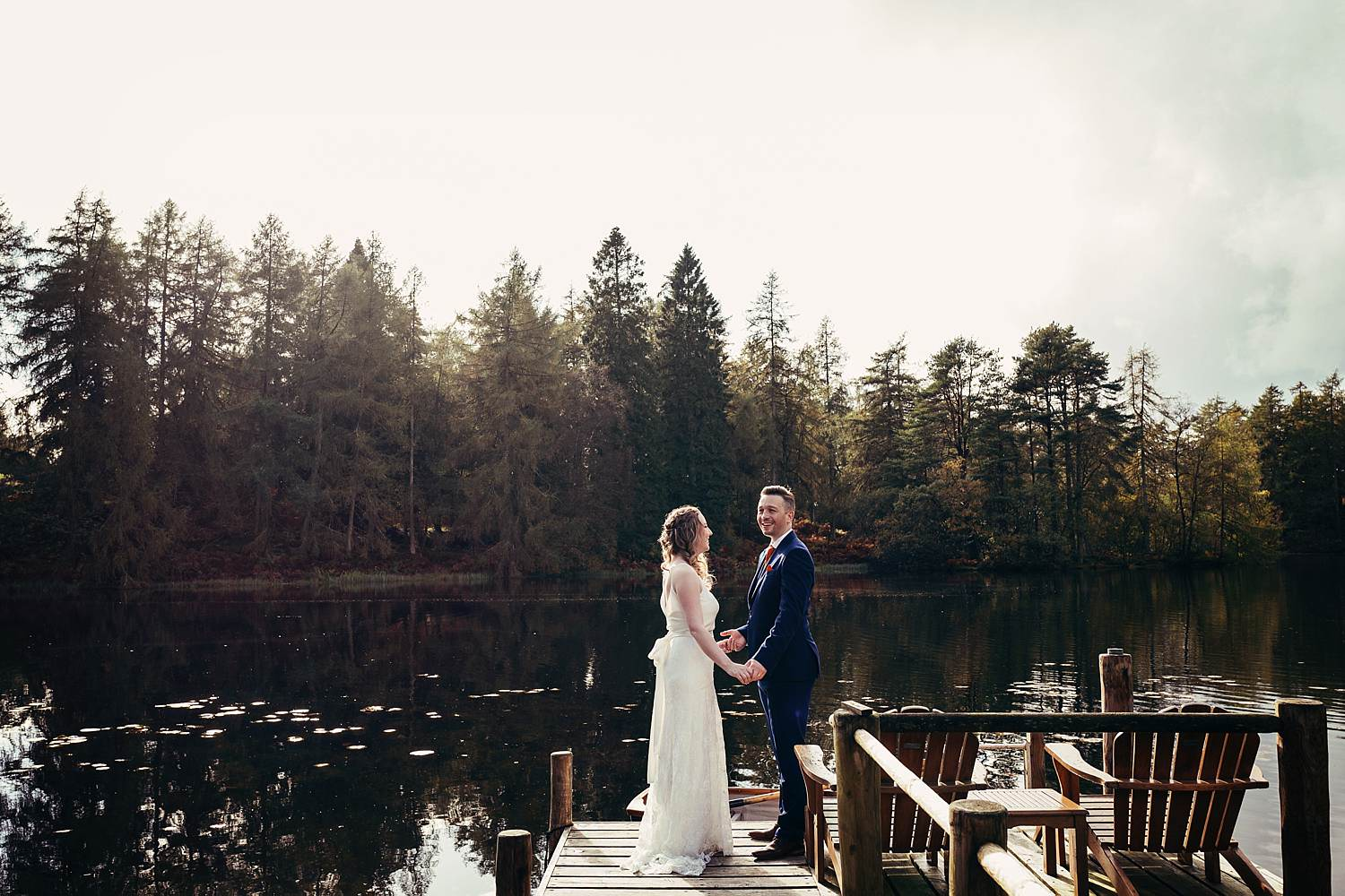 Bride and groom holding hands overlooking Knipe Tarn
