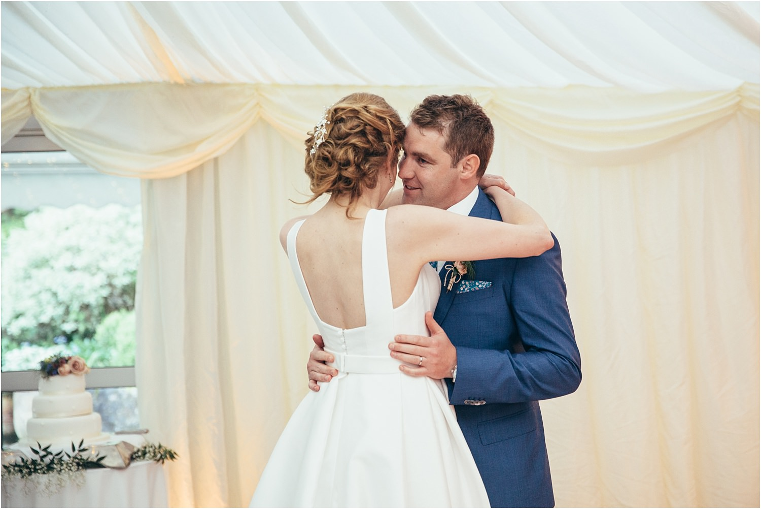Bride and groom lovingly embrace after cutting the cake at their Inn at Whitewell wedding reception