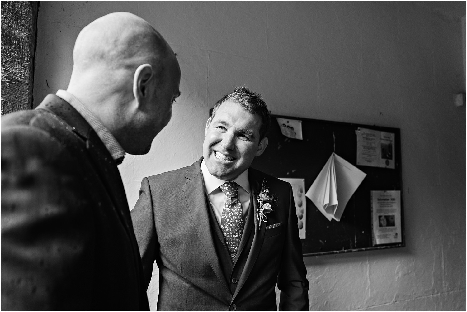 Groom greets guest in church doorway prior to his wedding in the Trough of Bowland