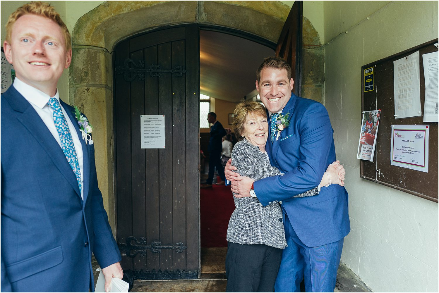 Bridegroom hugs guest at church door, prior to wedding in Trough of Bowland, Lancashire