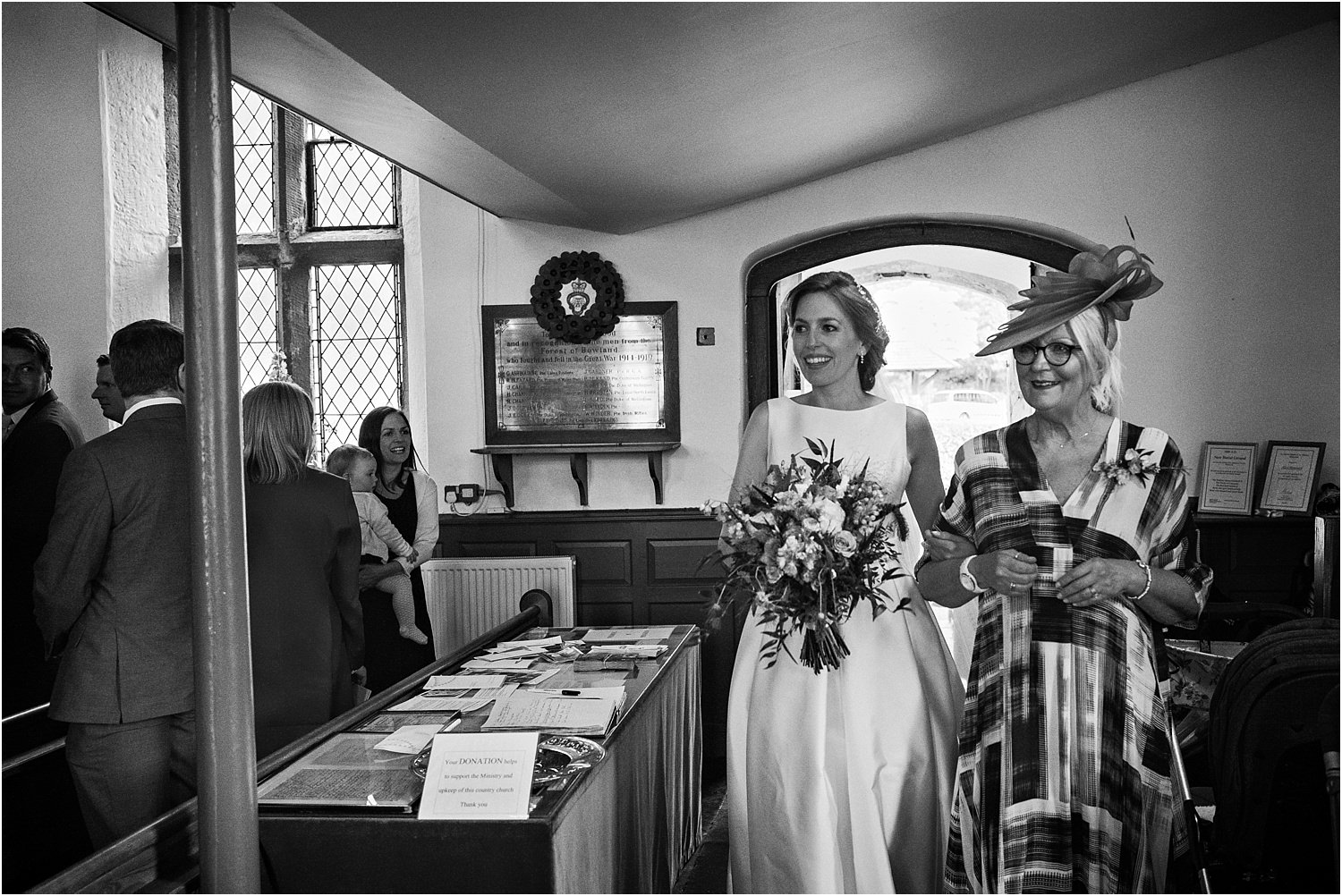 Bride enters Lancashire church for her ceremony with her mum on her arm.