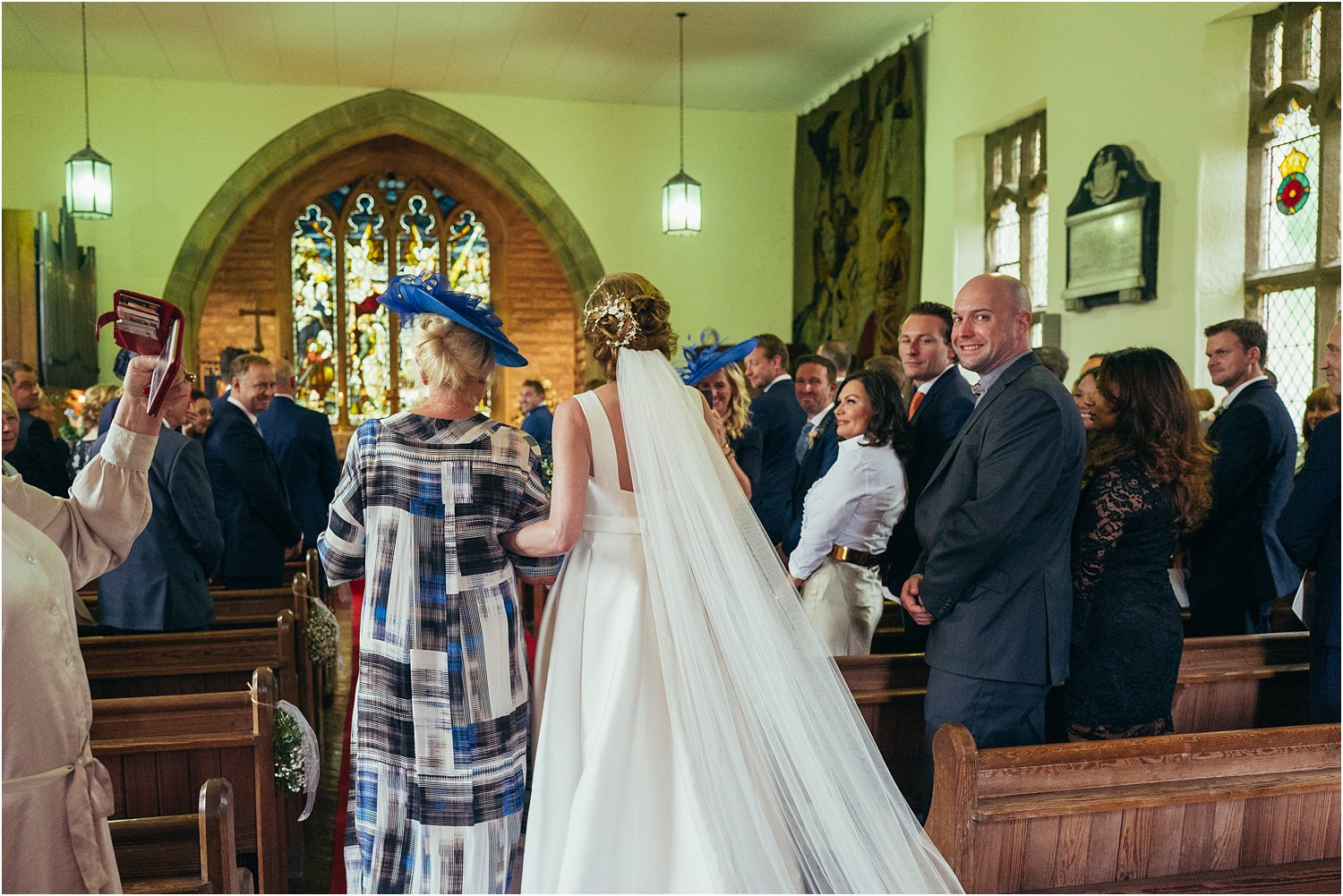 Bride walks down the aisle with her mum.
