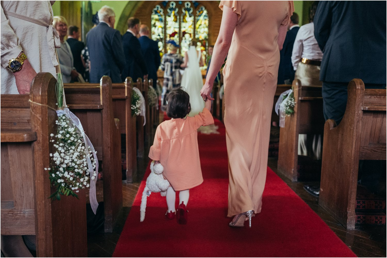 Little bridesmaid holding teddy walks down the aisle