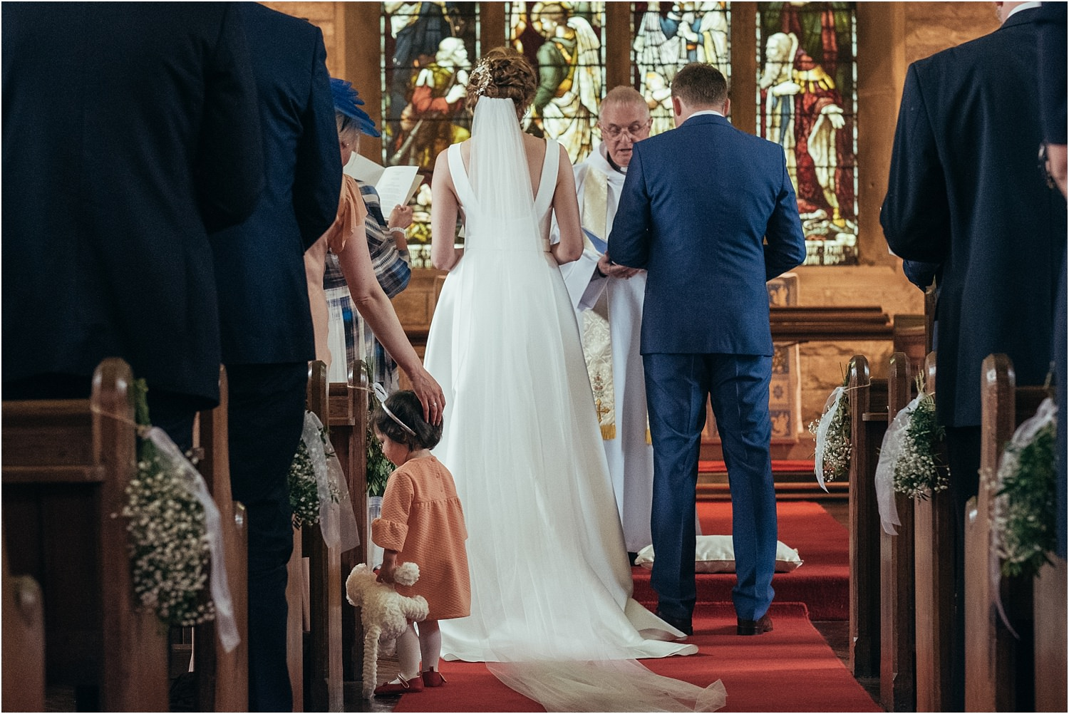 Rear view of bride and groom at the altar with little bridesmaid and teddy in the aisle