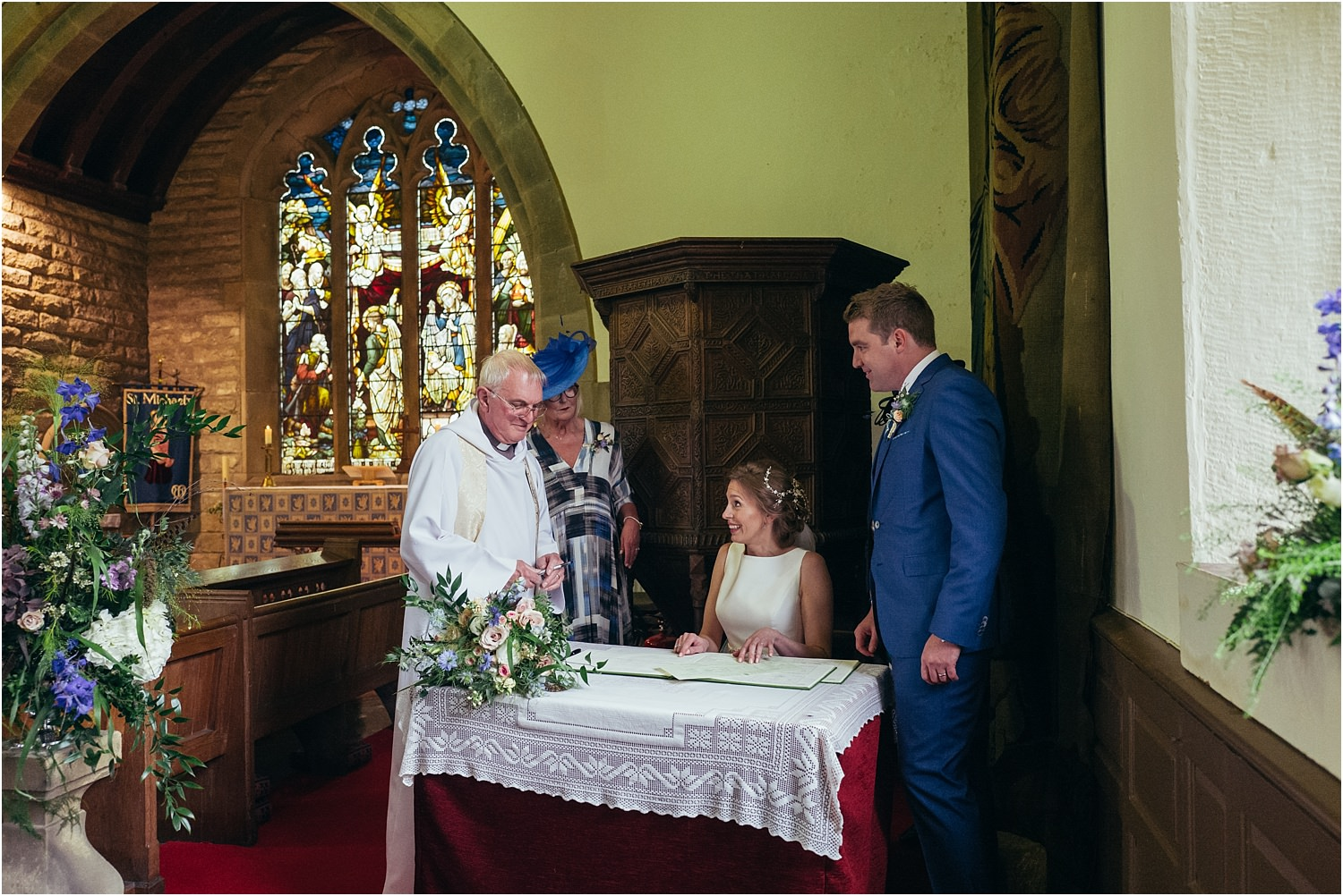 Bride, groom, vicar and bride's mum at the register signing in Lancashire church