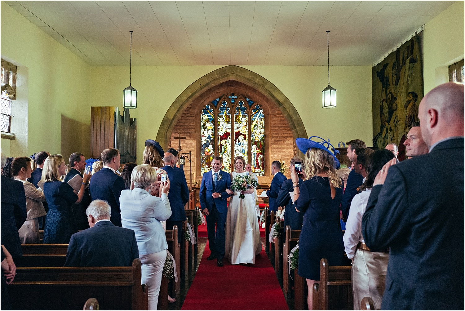 Bride and groom walking back down the aisle as man and wife in Lancashire church