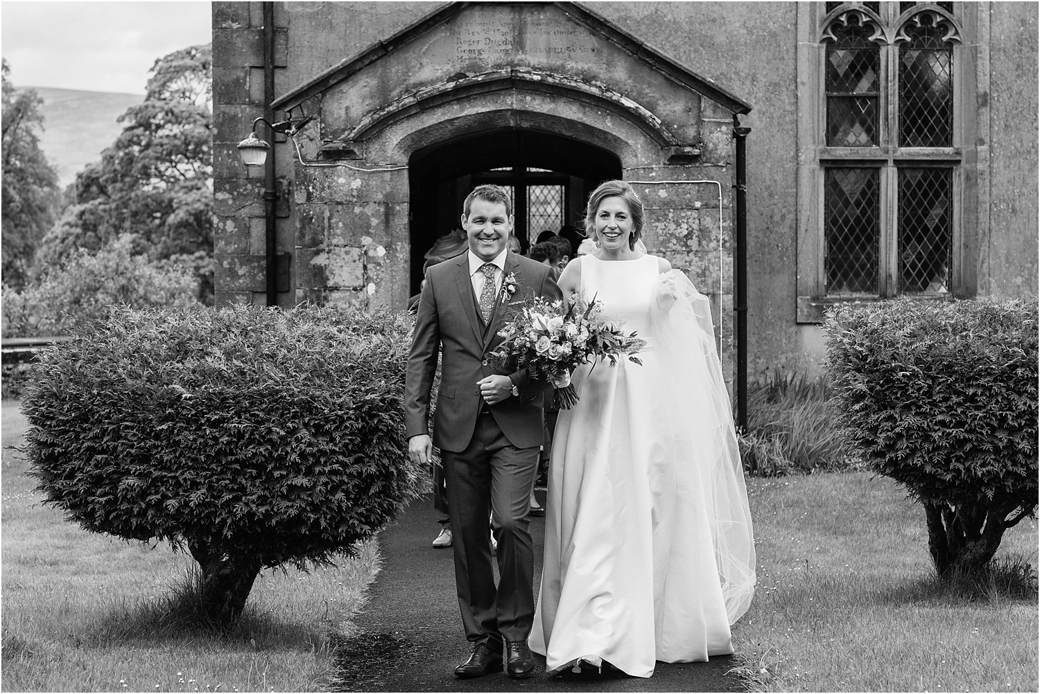 Bride and groom walking down the church path in the Trough of Bowland