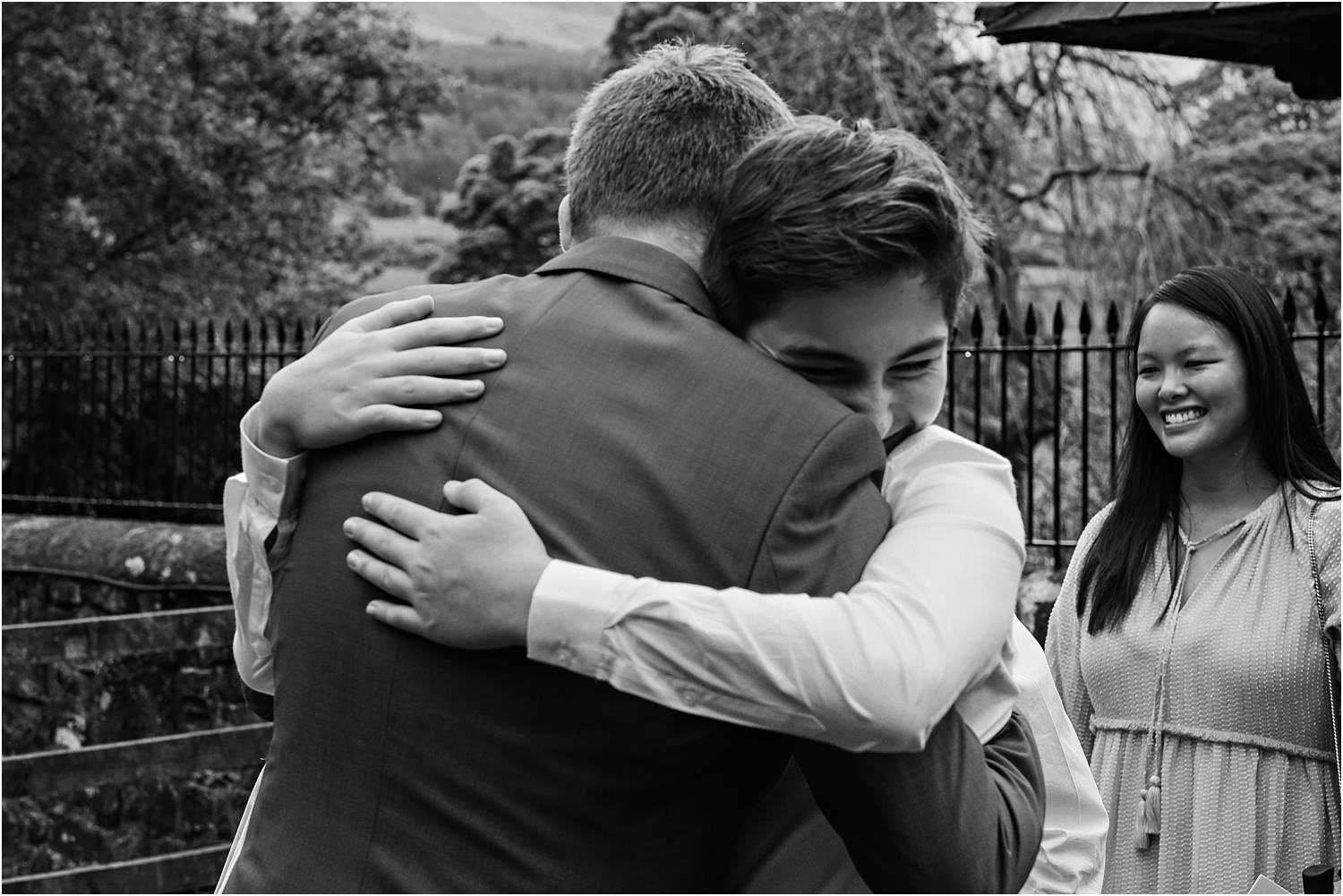 Young guest hugs bridegroom after wedding ceremony in Trough of Bowland, Lancashire