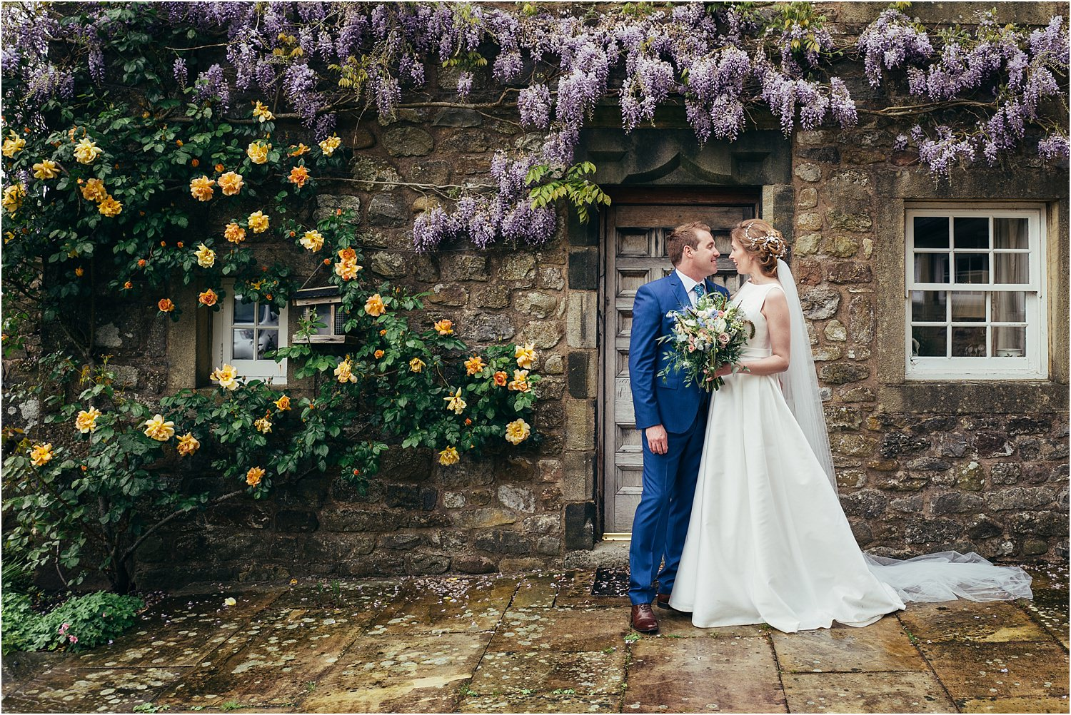 Bride and groom in front of the wisteria at the front door of The Inn at Whitewell