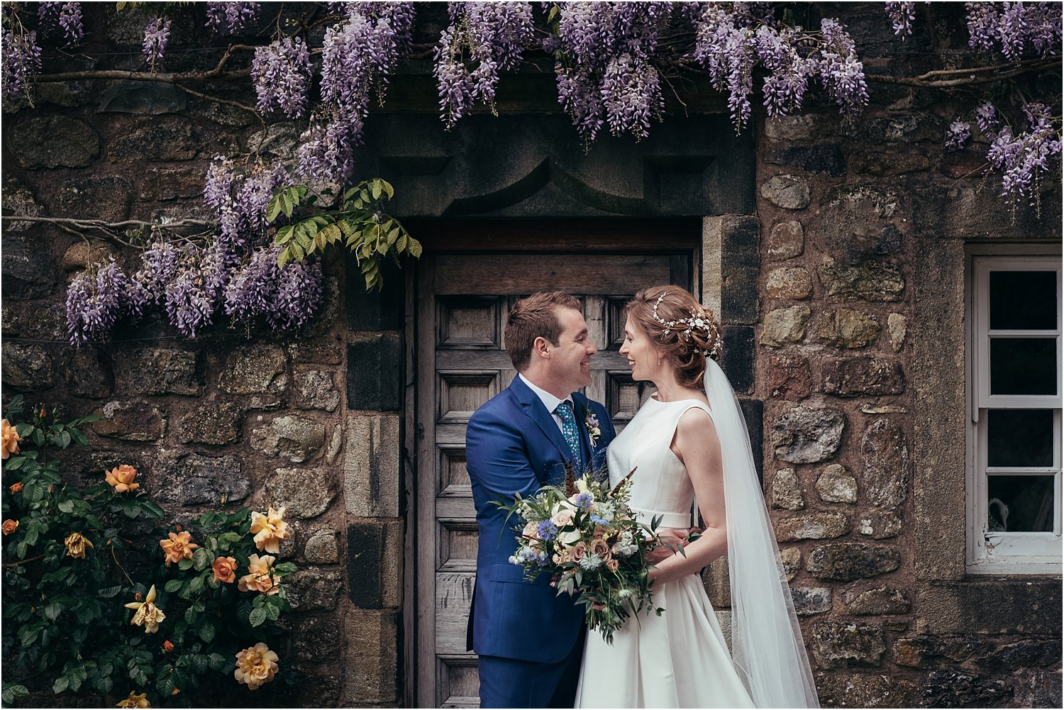 Bride and groom outside their wedding reception venue, The Inn at Whitewell in Lancashire