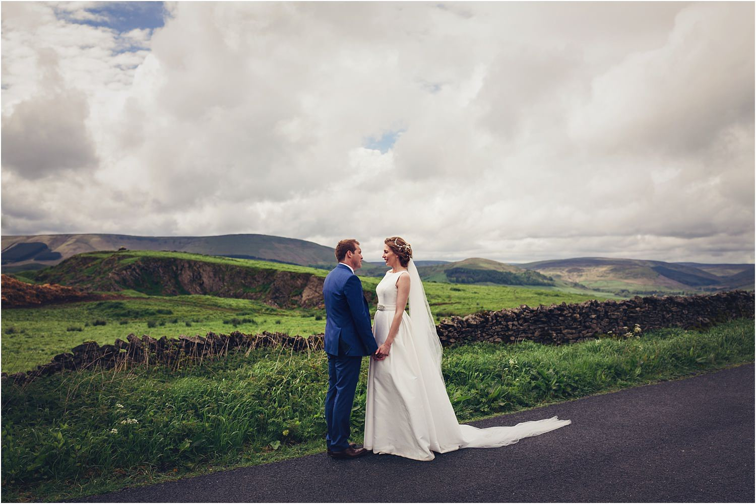Bride and groom on Lancashire lane with the Trough of Bowland in the background