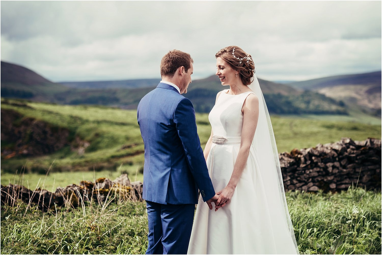 Bride in Jesus Peiro dress, shares a moment with her groom with the fells of the Trough of Bowland in the background