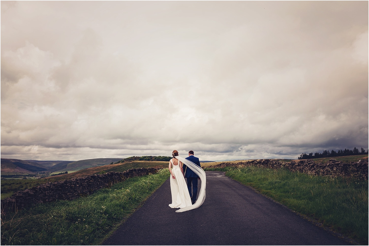 Bride and groom walking along Lancashire lane with Trough of Bowland in the background