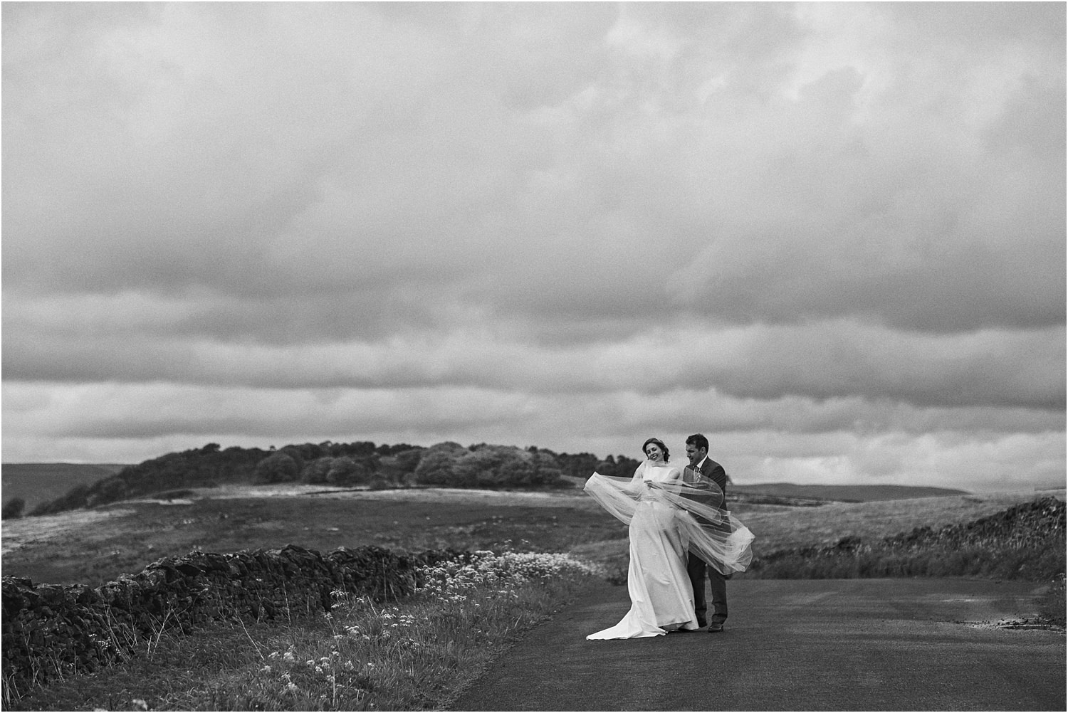 Bride and groom on rural Lancashire lane with veil blowing in the wind