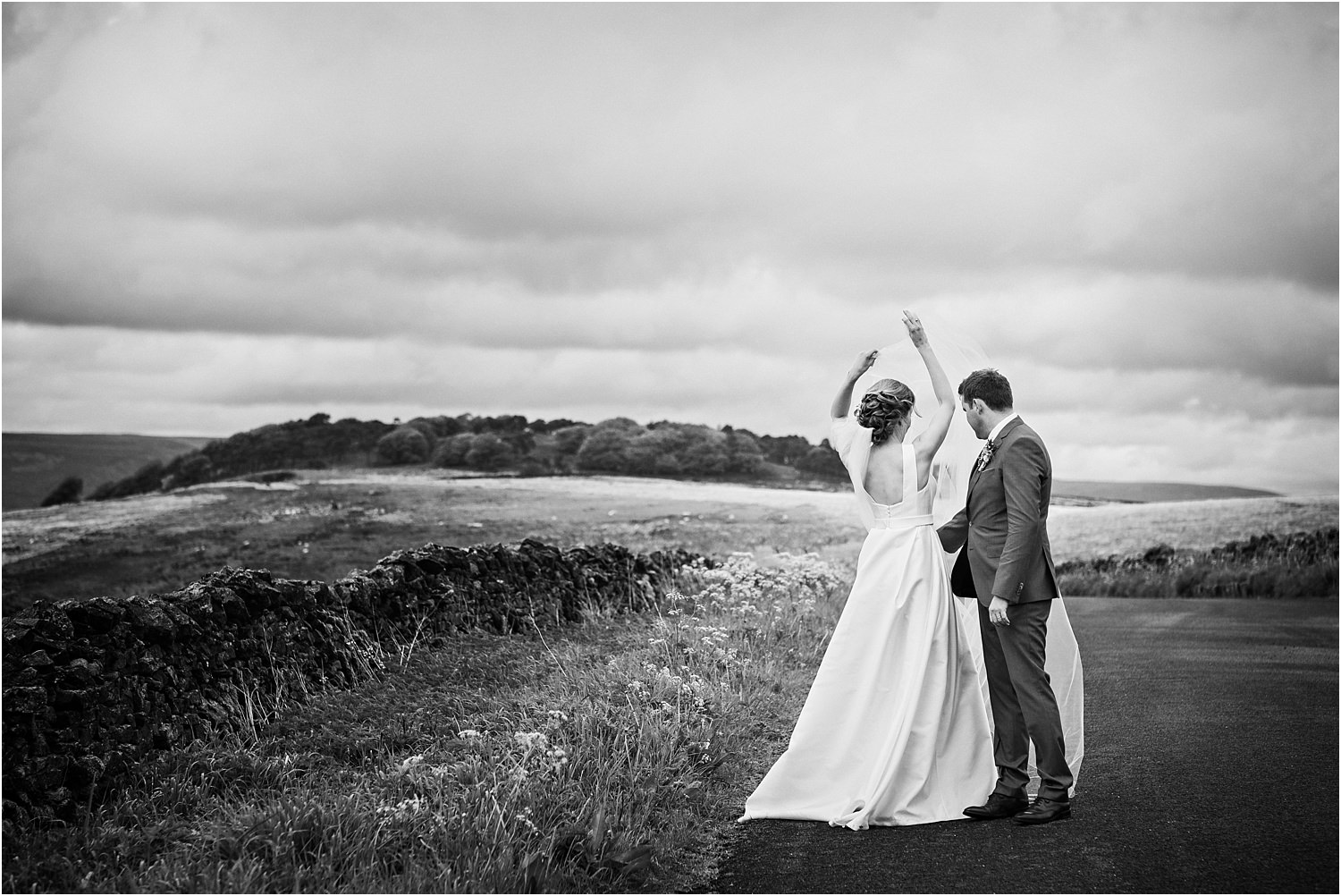 Bride does a twirl to unwrap her veil on windy Lancashire lane with her husband