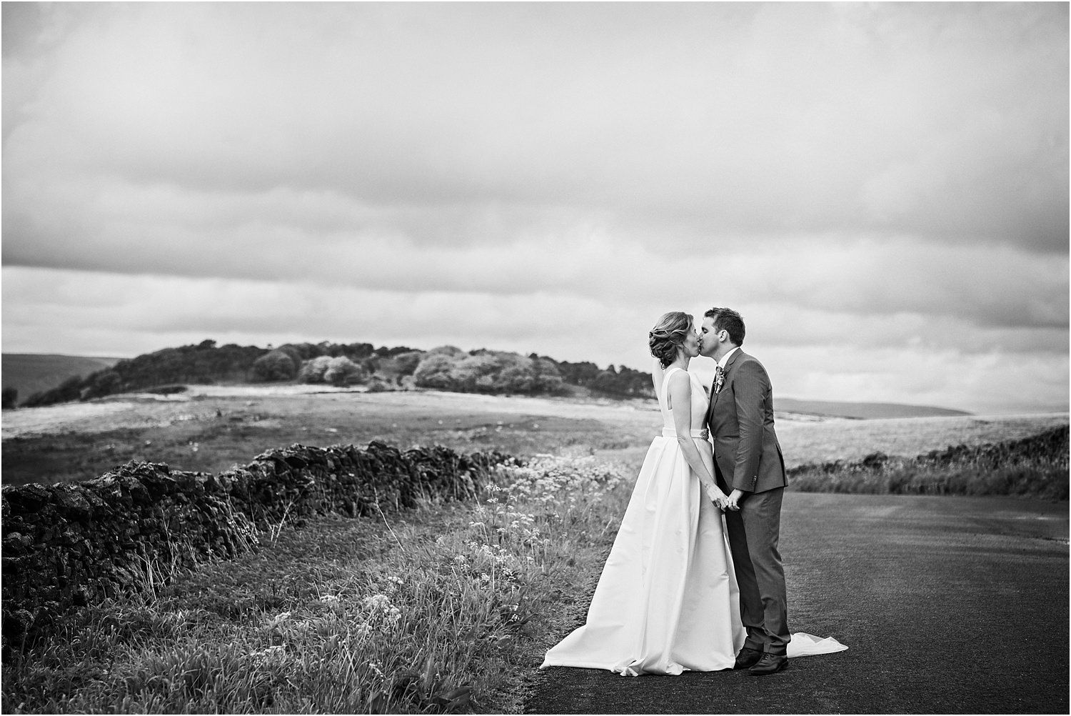 Bride and groom share a kiss on Lancashire fells in The Trough of Bowland