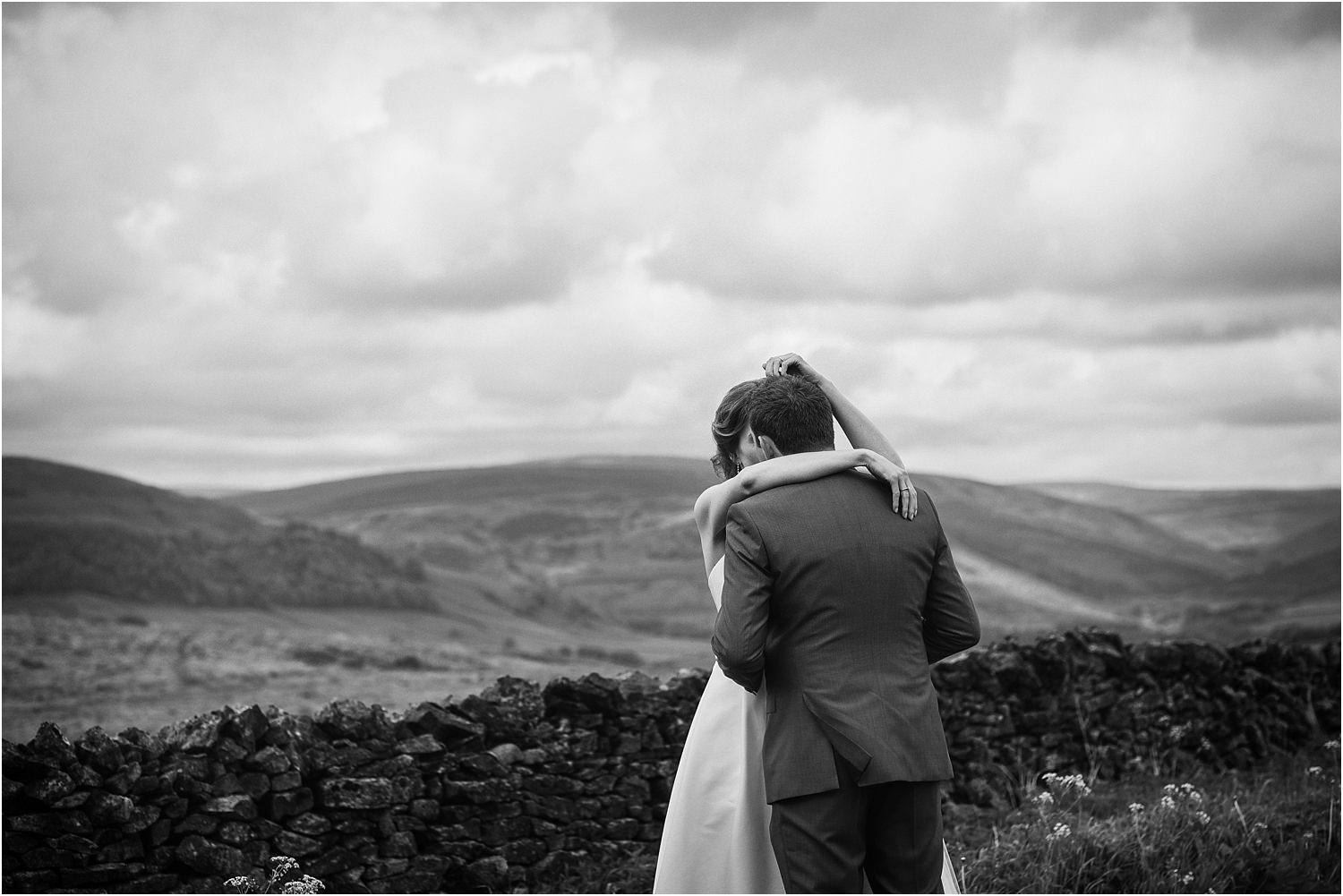 Brde and groom embrace after their wedding ceremony, with Lancashire fells in the bcakground