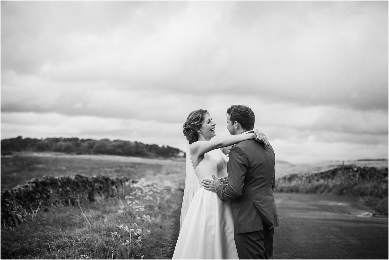 Lancashire hills provide the backdrop for bride and groom's embrace after their  wedding ceremony