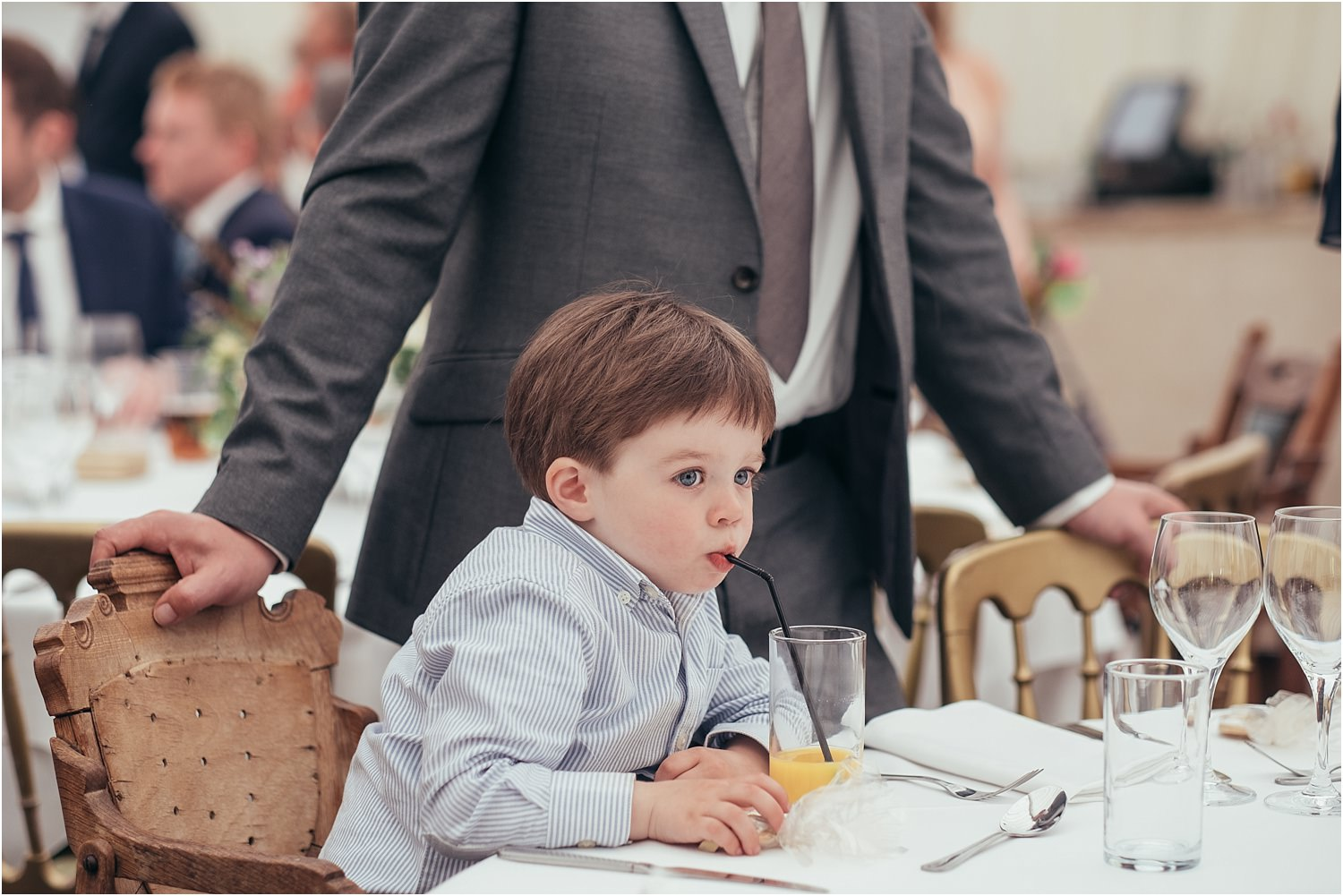 Junior guest with orange and a straw at wedding reception marquee in Lancashire