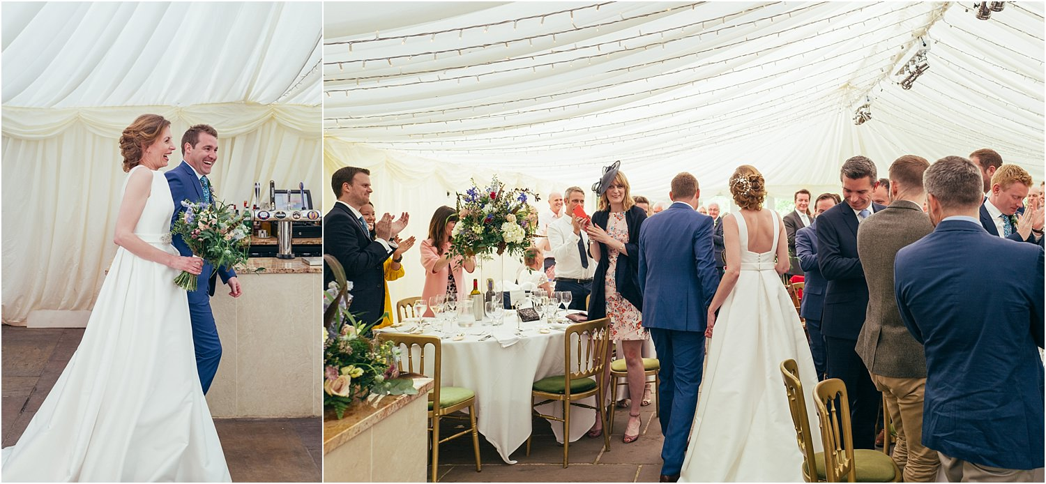 Guests stand to greet bride and groom as they enter the marquee for their reception at The Inn at Whitewell