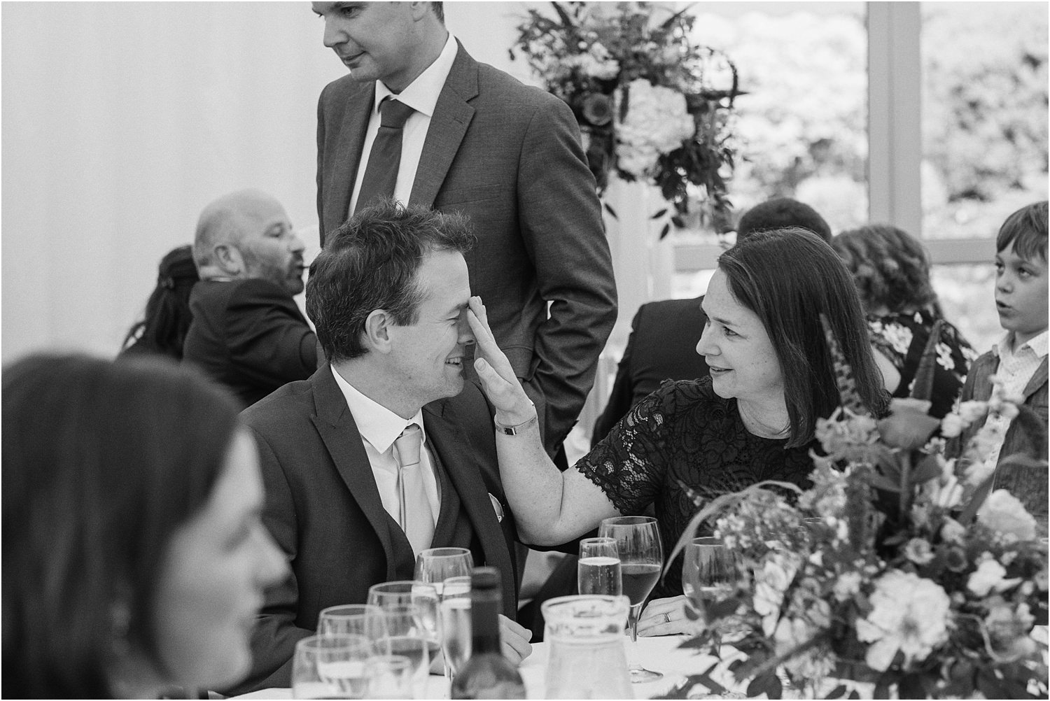 Guest touches partner's nose at wedding reception
