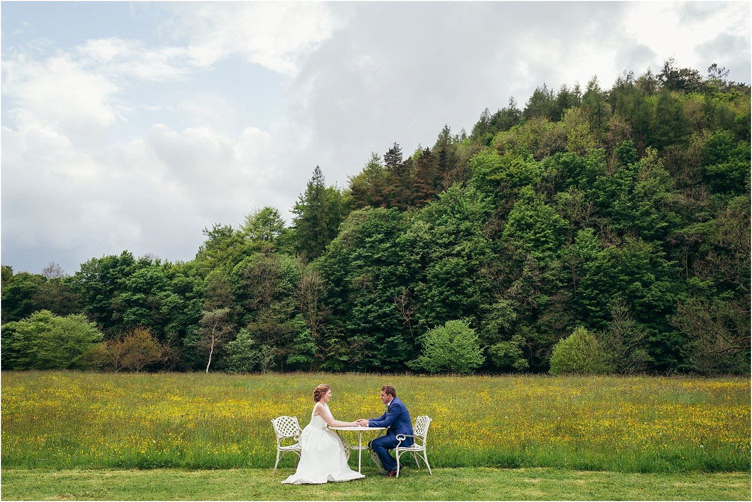 Bride and groom sitting outside at garden table with Trough of Bowland in the background