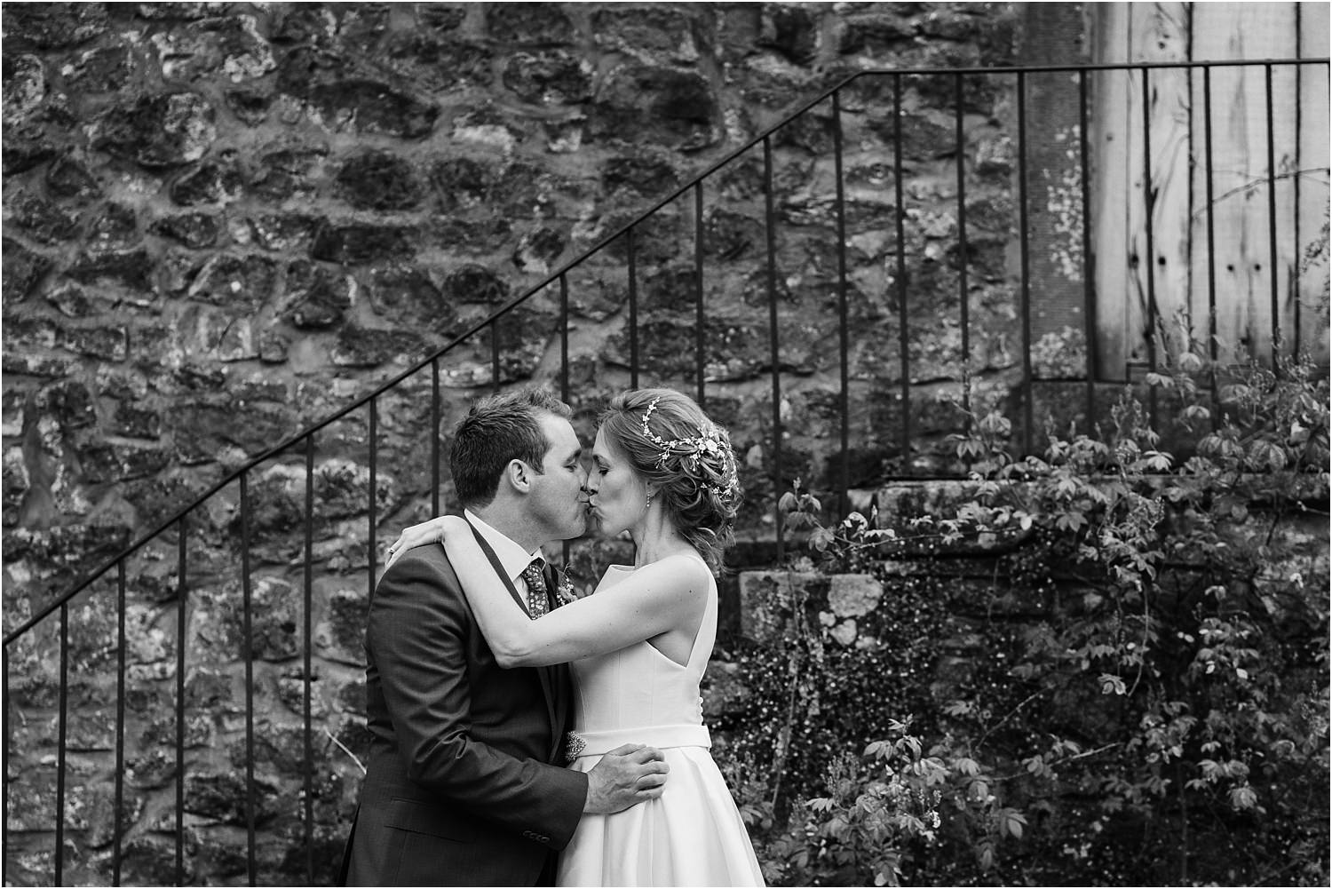 Bride and groom share a kiss at Lancashire wedding venue, The Inn at Whitewell