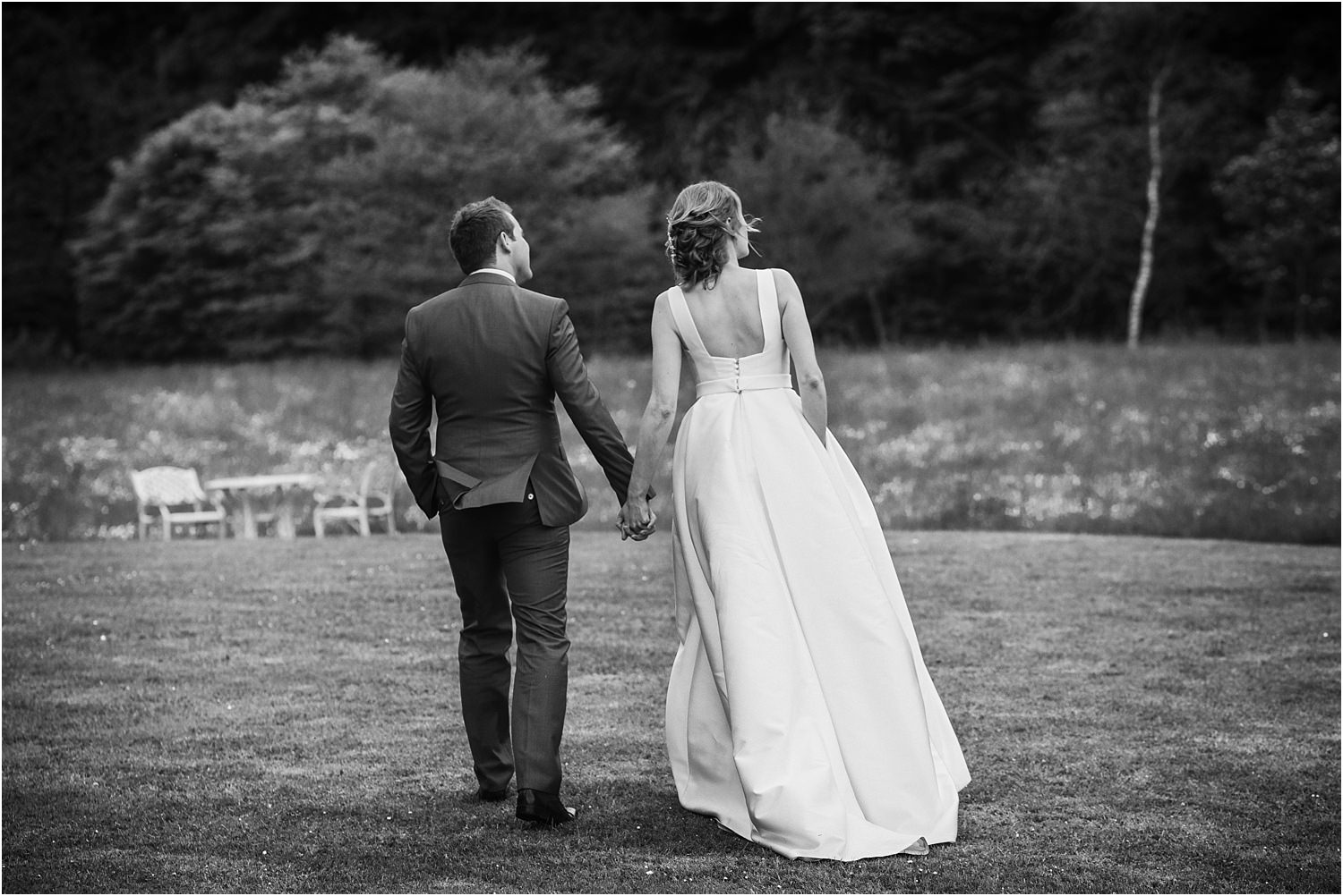Bridea nd groom walking across the gardens at The Inn at Whitewell after their wedding reception