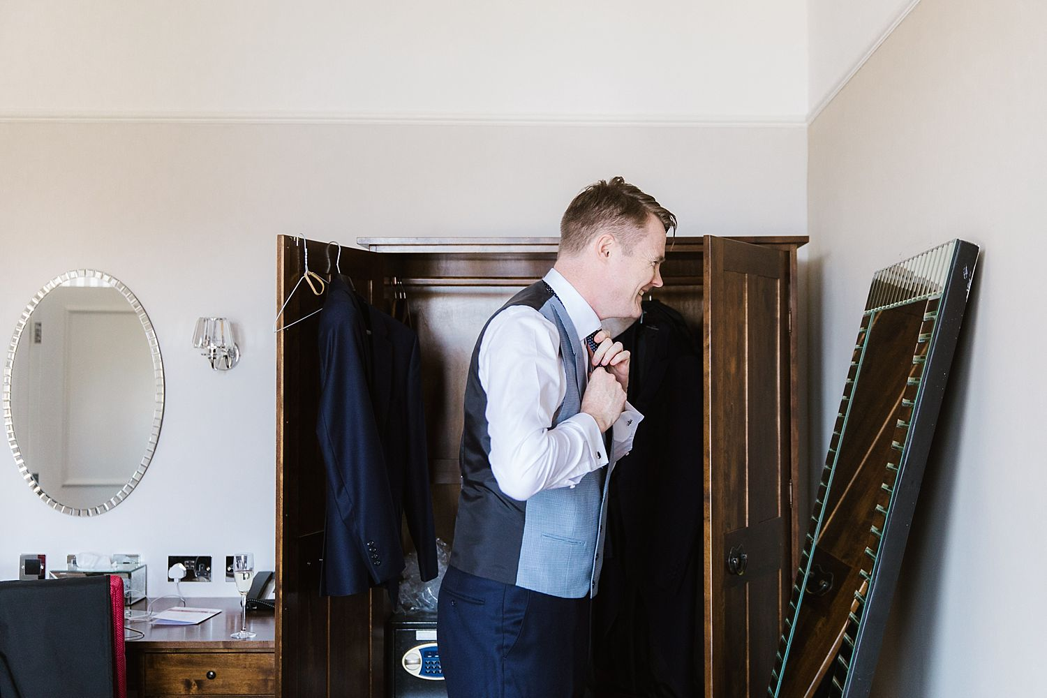 Groom adjusting tie at Belsfield hotel wedding