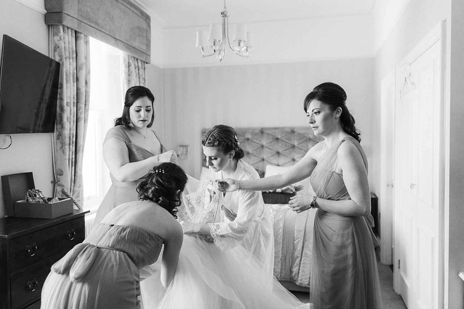 Bridesmaids preparing wedding dress for bride at Laura Ashley Belsfield Hotel, Bowness on Windermere