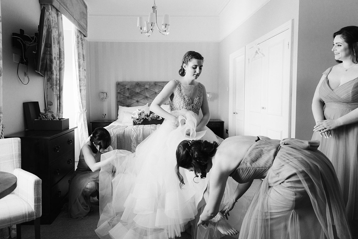 Bridesmaid helping bride with her garter, Lake Distric wedding at the Laura Ashley Belsfield Hotel