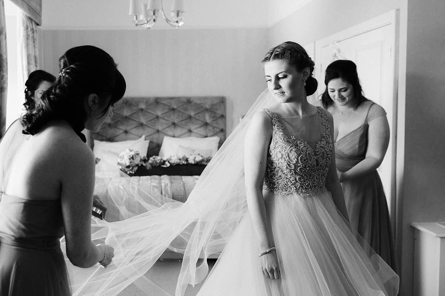 Bride and bridesmaids straightening veil at Belsfield Hotel wedding